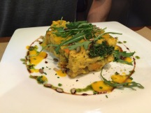 Cake of Millet with smoked eggplant tofu, kale and cabbage with carrot sauce and sweet potato.